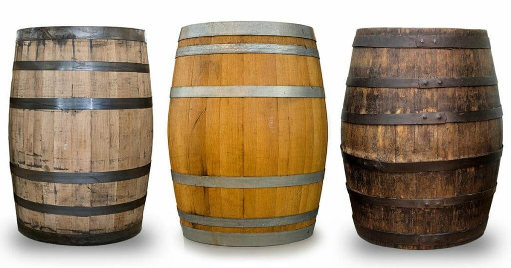 A wine, whiskey and bourbon barrel lined up next to each other to give a clear idea of the differences between barrel types.