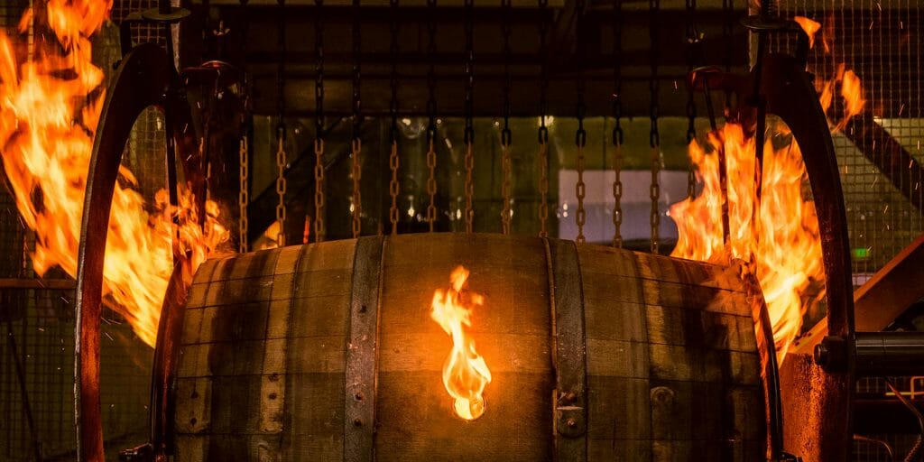 A used whiskey barrel getting charred after it was shaved as part of Country Connection's barrel refurbishing program